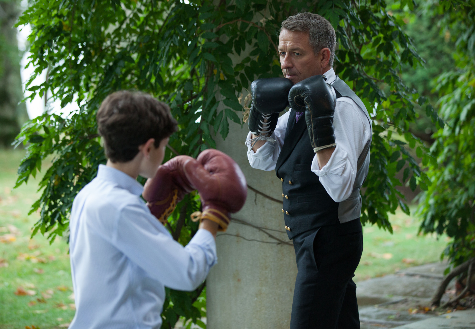 """GOTHAM: Alfred (Sean Pertwee, R) gives Bruce (David Mazouz, L) a lesson on fighting in the """"Harvey Dent"""" episode of GOTHAM airing Monday, Nov. 17 (8:00-9:00 PM ET/PT) on FOX. ©2014 Fox Broadcasting Co. Cr: Jessica Miglio/FOX"""